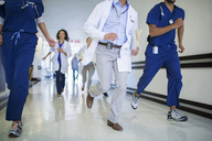 Doctors and nurses rushing in hospital hallway - CAIF08517