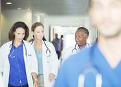 Doctors walking in hospital hallway - CAIF08526