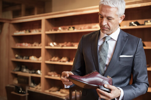Businessman shopping for dress shoes in menswear shop - CAIF08556