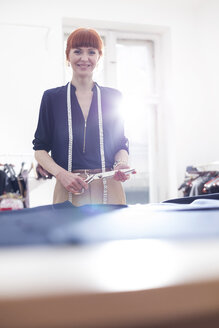 Portrait confident female tailor holding scissors in menswear workshop - CAIF08568