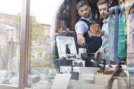 Worker showing businessman merchandise in window of menswear shop - CAIF08571