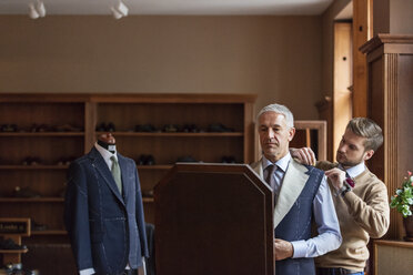 Tailor fitting businessman for suit in menswear shop - CAIF08577