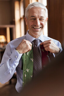 Smiling businessman trying on ties in mirror at menswear shop - CAIF08586
