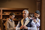 Tailors fitting businessman for suit in menswear shop - CAIF08592