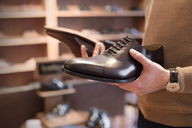 Businessman browsing dress shoes in menswear shop - CAIF08604