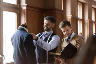 Tailors examining suit and taking notes in menswear shop - CAIF08607