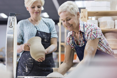 Senior woman holding pottery at kiln in studio - CAIF08625
