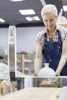 Senior woman placing pottery in kiln in studio - CAIF08637