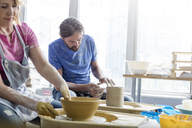 Mature couple using pottery wheels in studio - CAIF08655