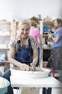 Portrait smiling senior woman using pottery wheel in studio - CAIF08661