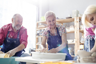 Smiling senior couple using pottery wheels in studio - CAIF08673