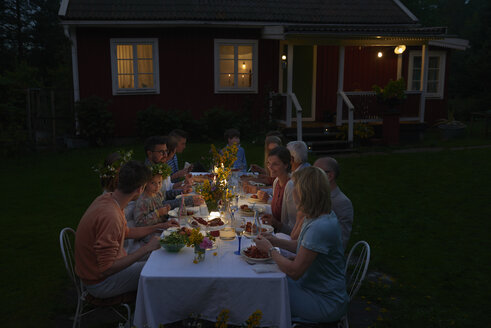 Family enjoying candlelight dinner at patio table outside house at night - CAIF08718