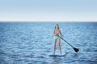 Young woman in bikini paddleboarding on summer ocean - CAIF08784