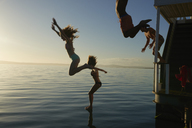 Young adult friends jumping from summer houseboat into sunset ocean - CAIF08787