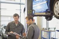 Mechanics reviewing paperwork in auto repair shop - CAIF08796