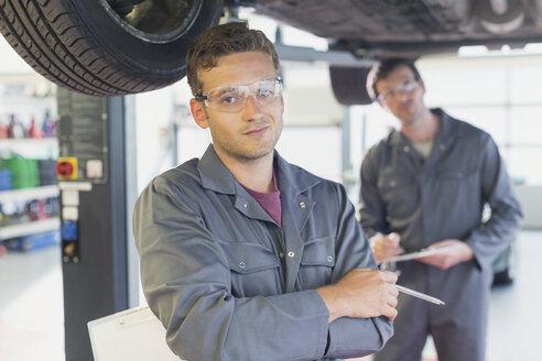 Portrait confident mechanic under car in auto repair shop - CAIF08802