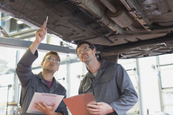 Mechanics with clipboards working under car in auto repair shop - CAIF08808