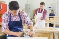 Carpenter using plane tool in workshop - CAIF08811