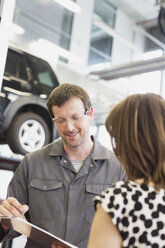 Mechanic with clipboard talking to customer in auto repair shop - CAIF08814