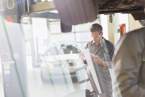 Mechanic with clipboard under car in auto repair shop - CAIF08820