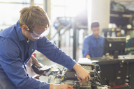 Mechanic working on engine in auto repair shop - CAIF08835
