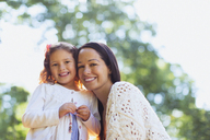 Portrait smiling mother and daughter outdoors - CAIF08844