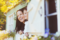 Smiling mother and daughter in playhouse window - CAIF08850