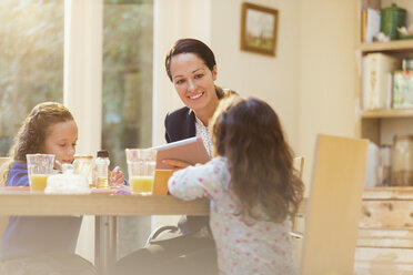 Working mother and daughters at breakfast table - CAIF08853