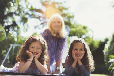 Portrait smiling grandmother with twin granddaughters in park - CAIF08856