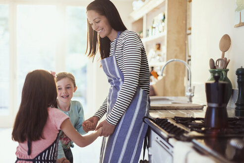 Mother and daughters holding hands in kitchen - CAIF08877