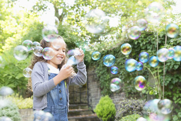 Girl blowing bubbles in backyard - CAIF08880