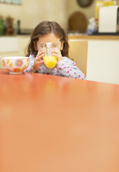 Girl drinking orange juice at breakfast table - CAIF08886