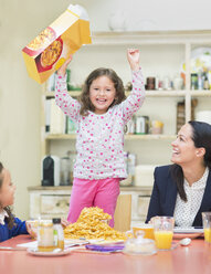 Portrait enthusiastic girl cheering with cereal box at breakfast table - CAIF08889