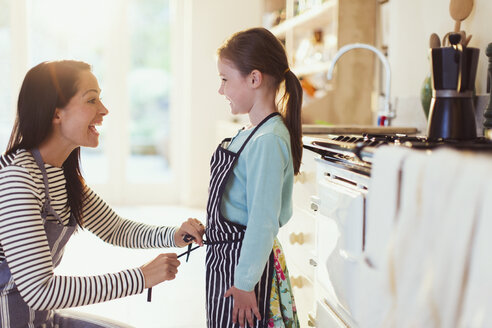 Mother tying apron on daughter in kitchen - CAIF08895