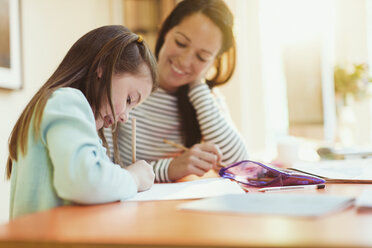 Mother watching daughter do homework - CAIF08898