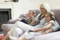 Grandmother and granddaughters watching TV on living room sofa - CAIF08901