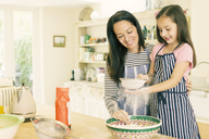 Mother and daughter baking sifting flour in kitchen - CAIF08910