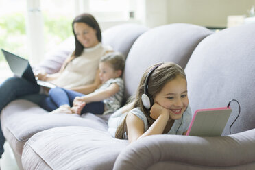 Girl with headphones and digital tablet laying on living room sofa - CAIF08916
