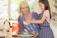 Grandmother and granddaughter baking sifting flour in kitchen - CAIF08928
