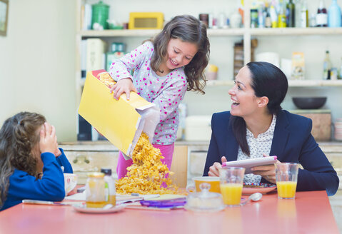 Playful girl pouring abundance of cereal onto breakfast table - CAIF08931