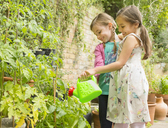 Hugging girls watering plants in garden - CAIF08937