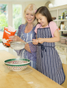 Grandmother and granddaughter baking sifting flour in kitchen - CAIF08940