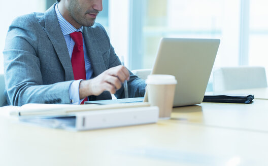 Focused businessman working at laptop in conference room - CAIF08949