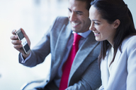 Businessman showing cell phone video to businesswoman - CAIF08964