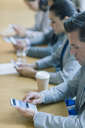 Businessman using cell phone in conference room - CAIF08979