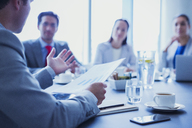 Businessman leading meeting explaining paperwork in conference room - CAIF08985