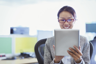 Smiling businesswoman using digital tablet in office - CAIF08991