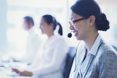 Smiling businesswoman talking on the phone with headset - CAIF09000