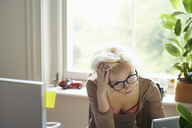 Stressed woman with hands in hair working in office - CAIF09009