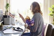 Woman receiving flower bouquet and reading card in home office - CAIF09012